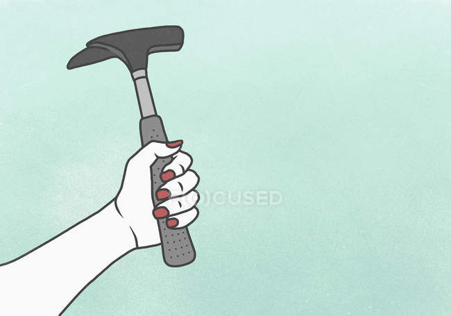 Crop female hand holding hammer against blue background — Stock Photo