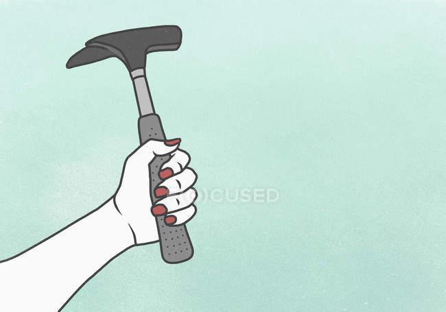 Обтинання жіночий руки, що тримає молотом тлі синього — стокове фото
