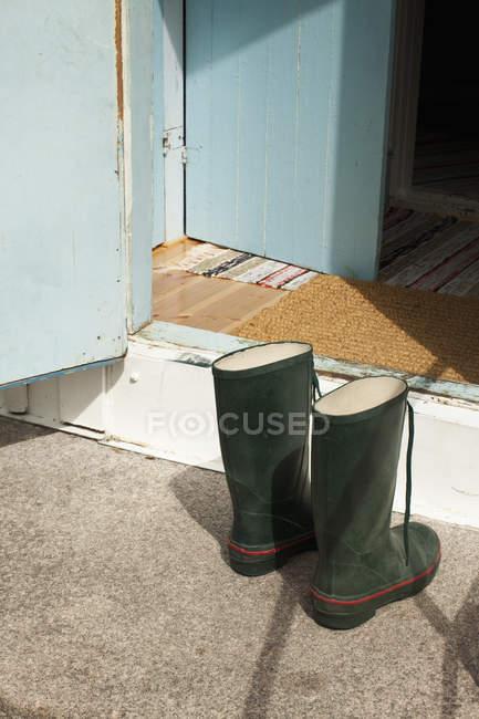Two wellington boots in front of open door — Stock Photo