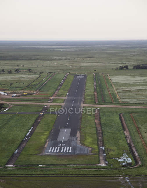 Vista aérea da pista do aeroporto em meio ao campo rural no dia nublado — Fotografia de Stock