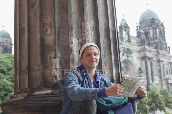 Portrait en angle bas d'un jeune touriste assis avec carte au Altes Museum, Berlin, Allemagne — Photo de stock