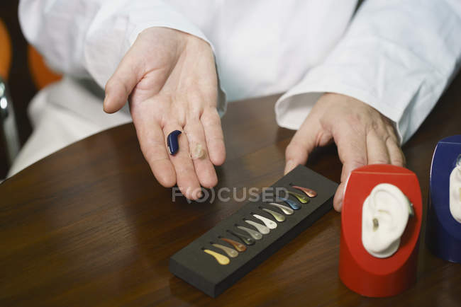 Crop audiologist showing hearing aid at table — Stock Photo