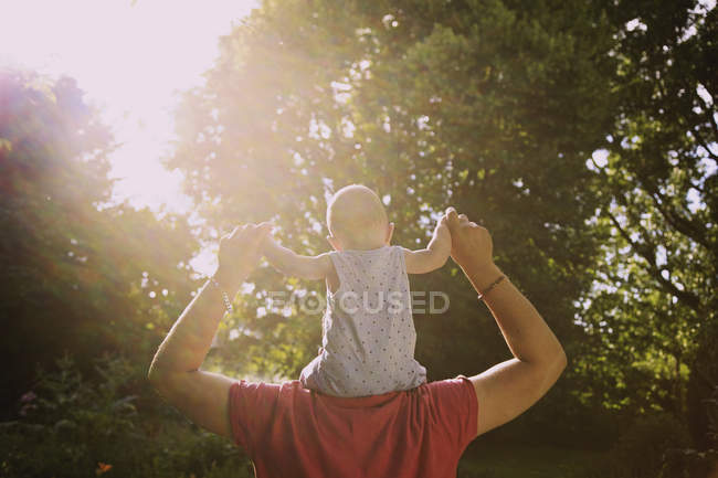 Rear view of father carrying baby boy on shoulders at yard during sunny day — Stock Photo