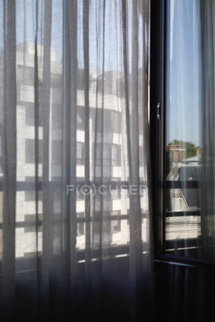 Vista sulla facciata dell'edificio illuminata dal sole vista attraverso la tenda — Foto stock