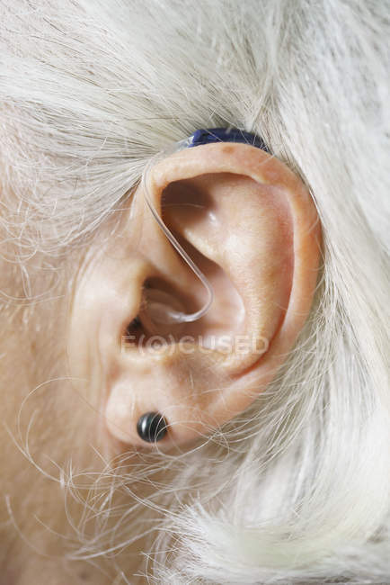 Close up view of senior woman's ear wearing hearing aid — Stock Photo