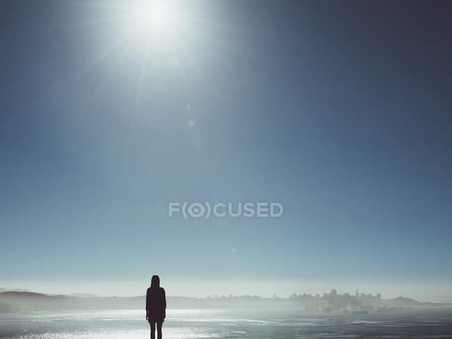 Силует жіночий погляд на Туманний міський пейзаж проти чистого неба на сонячний день — стокове фото