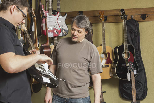 Mature male owner looking at young man examining electric guitar at store — Stock Photo