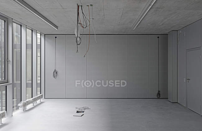 Interior of empty office with cables hanging from ceiling — Stock Photo