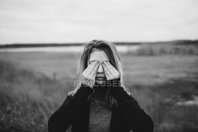 Ragazza adolescente che copre gli occhi mentre in piedi sul campo contro il cielo — Foto stock
