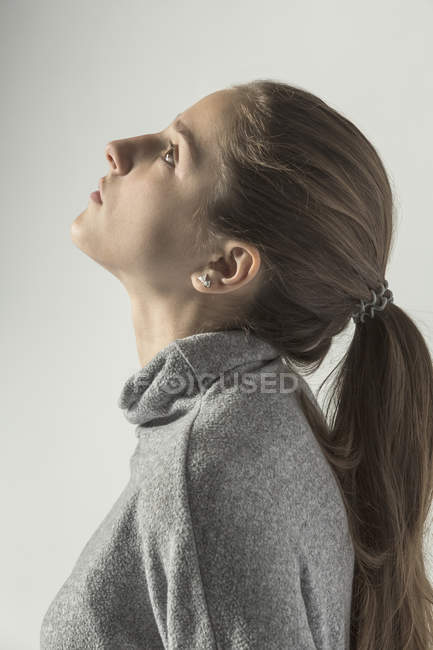 Profile of teenage girl looking up against white background — Stock Photo