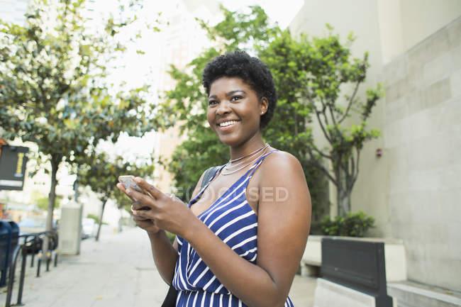 Sorrindo jovem mulher usando telefone celular na cidade — Fotografia de Stock