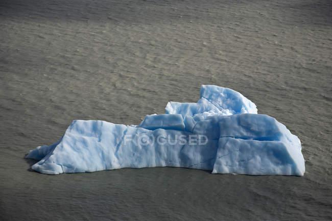 Vista distante de iceberg flutuando na água ondulada — Fotografia de Stock