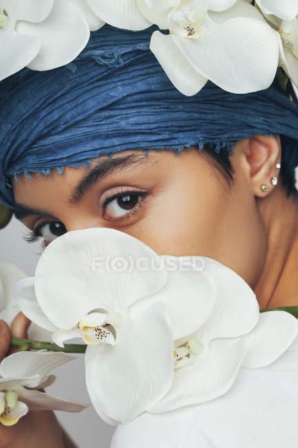 Retrato de mulher escondida atrás de orquídeas brancas frescas — Fotografia de Stock