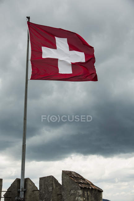 Swiss Flag on rooftop flapping in wind over cloudy sky — Foto stock