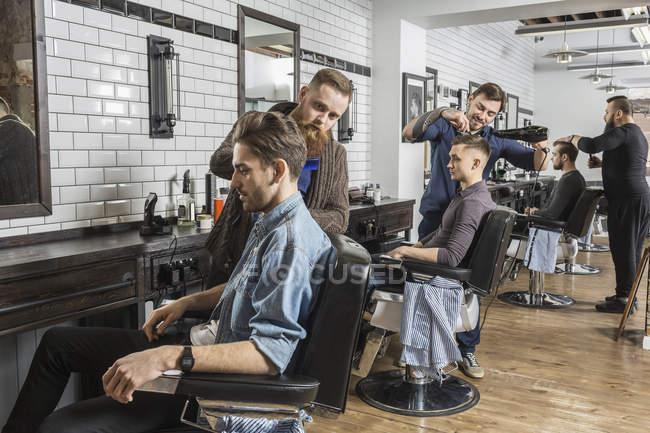 Coiffeurs coupe les cheveux du client masculin dans le salon — Photo de stock