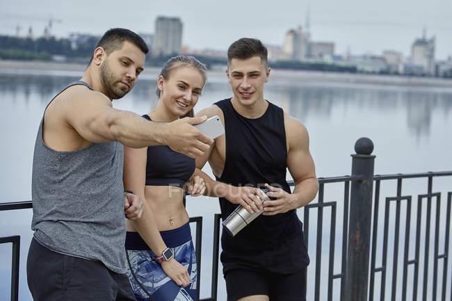 Atleta sorridente maschio scattare selfie con gli amici mentre in piedi contro il lago — Foto stock