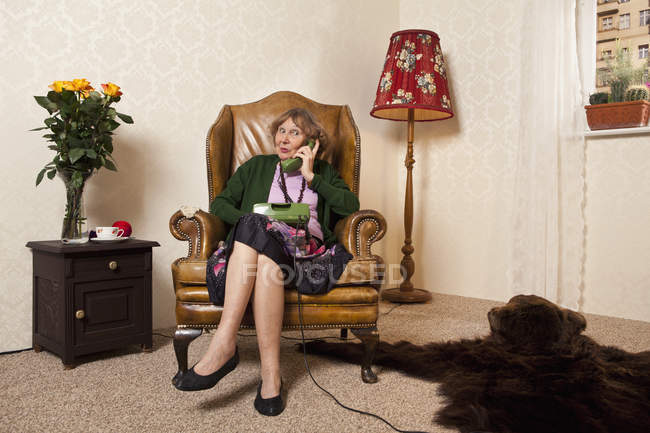 Senior woman gossiping on the phone in armchair in living room — Stock Photo