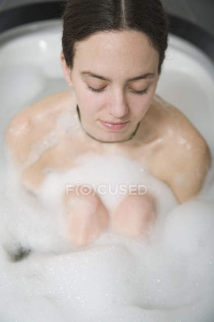 Woman with brown hair sitting in bath hugging knees — Stock Photo