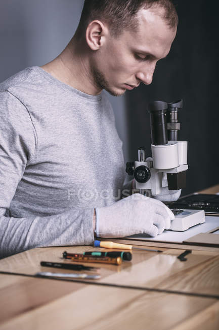Young male technician examining circuit board with microscope at electronics store — Stock Photo