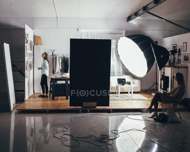 Female fashion designer and trainee with illuminated strobe lights in clothing studio — Stock Photo