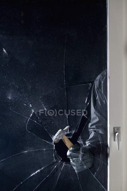 Criminal breaking window with hammer — Stock Photo