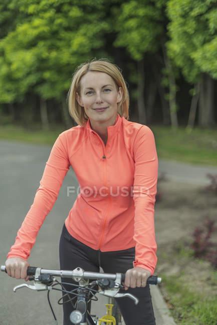 Retrato de mulher sorridente com bicicleta no caminho no parque — Fotografia de Stock