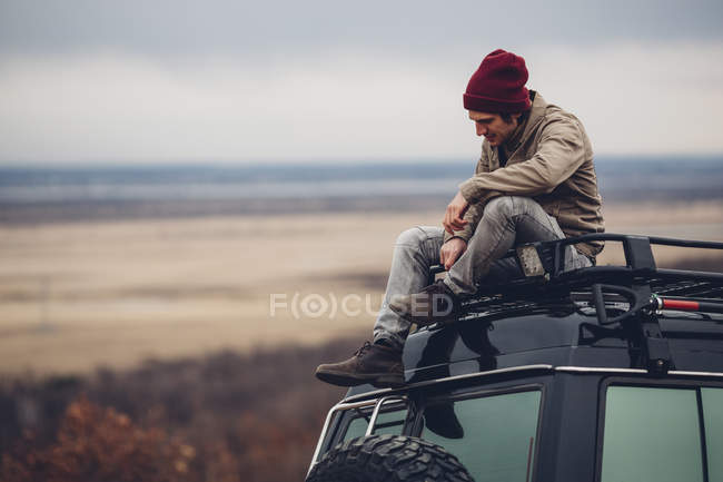 Man sitting on top of sports utility vehicle against landscape — Stock Photo