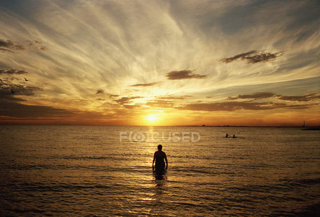 Silhouette of man standing in sea at sunset — Stock Photo