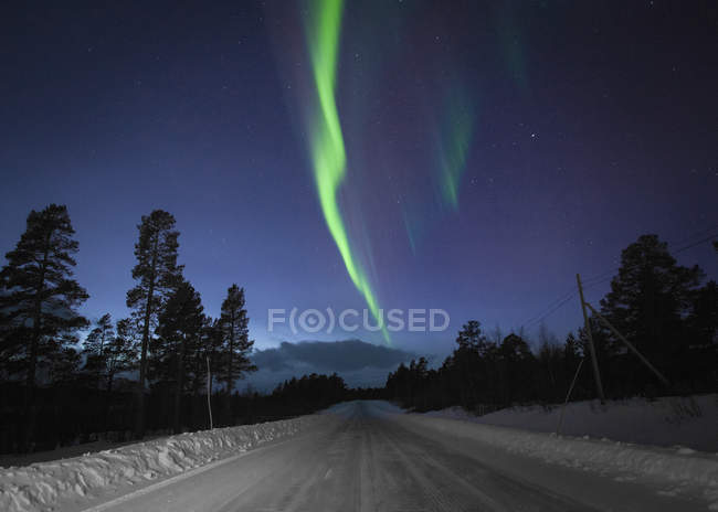 Scenic view of Aurora Borealis over snow covered road  at night — Stock Photo