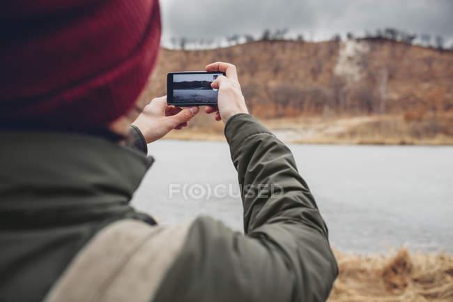 Задній вид людини фотографування озеро через смарт-телефон — стокове фото