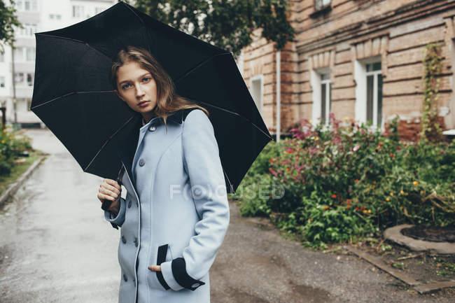 Portrait d'une adolescente tenant un parapluie debout dans la rue en ville — Photo de stock