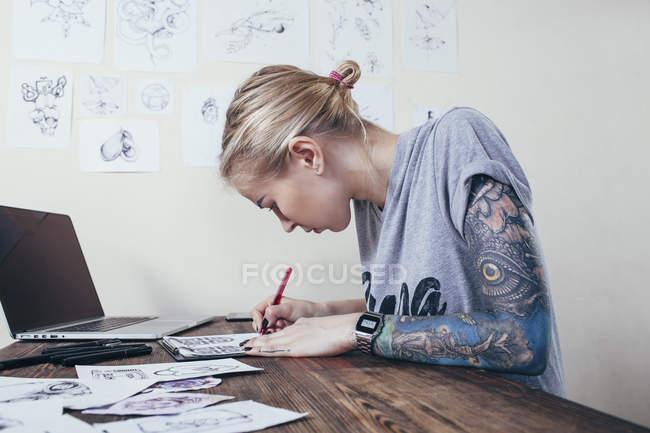 Tatuaggio artista fiducioso che lavora su disegni da laptop presso lo studio d'arte — Foto stock