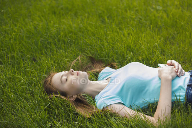 Young woman resting with eyes closed on grassy field — Stock Photo