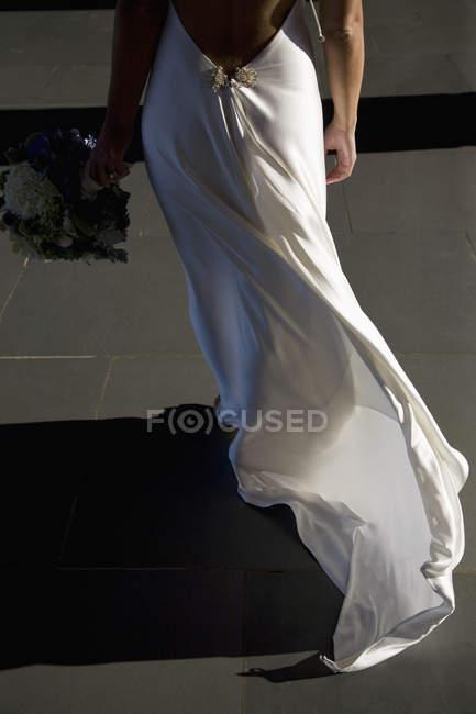 Vista traseira da noiva andando com flores na mão — Fotografia de Stock