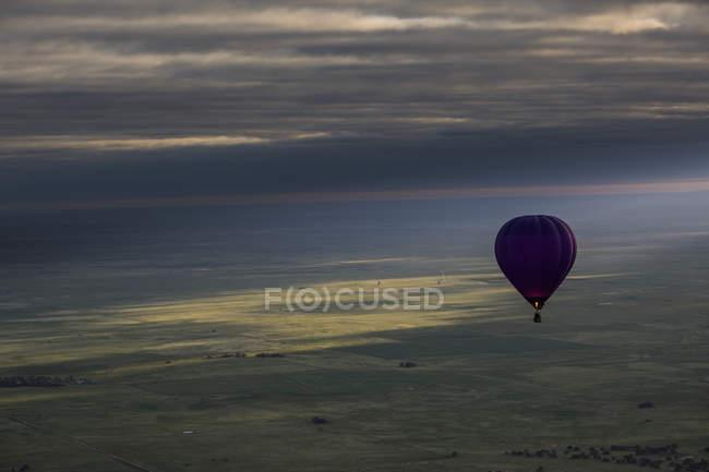 Globo de aire caliente sobre paisaje contra el cielo nublado durante puesta del sol - foto de stock