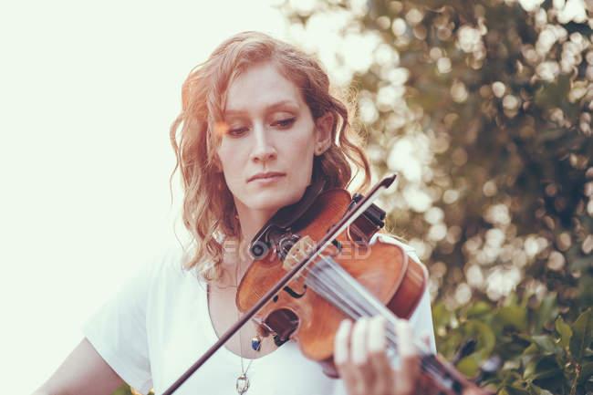 Mujer segura con el pelo ondulado tocando violín contra las plantas - foto de stock