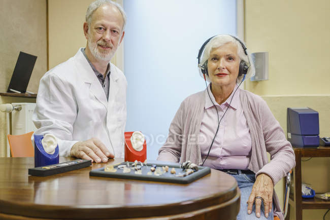 Portrait of audiologist and senior patient wearing headphones during ear exam at clinic — Stock Photo