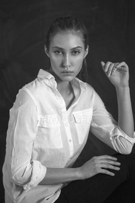 Portrait of confident fashion model against black background — Stock Photo