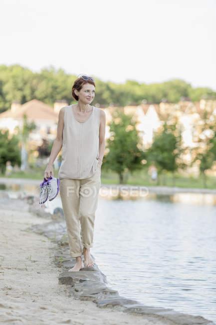 Женщина, идущая в воде по берегу озера против ясного неба — стоковое фото