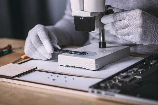 Detail image of technician examining random access memory with microscope at electronics store — Stock Photo