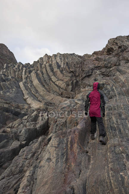 Rear view of person hiking up rocky mountain — Stock Photo