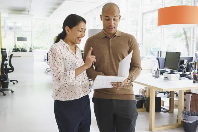 Бізнесмен показ файл для усміхнене жіночий колега в творчих office — стокове фото