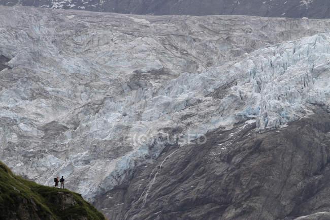 Vista de dos excursionistas en Glaciar enorme - foto de stock