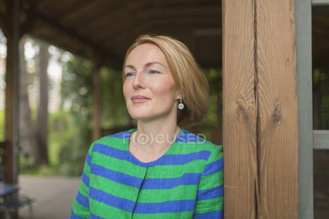 Mujer pensativa apoyada en la pared de madera en mirador en el parque - foto de stock