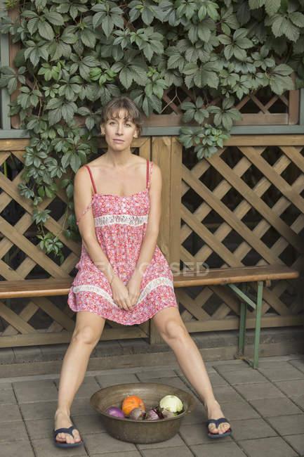 Ritratto di donna con ciotola di verdure seduto contro il recinto di legno — Foto stock