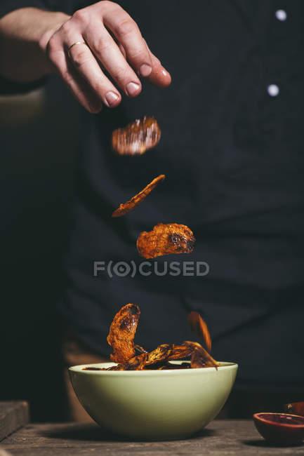 Mittelteil des Mannes wirft geröstete Orangenschale in Schüssel auf Tisch — Stockfoto