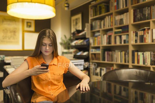 Молода жінка за допомогою телефону під час відпочинку на крісло на освітленій бібліотека — стокове фото