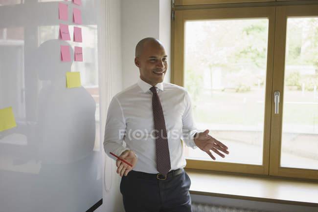 Fiducioso uomo d'affari che spiega accanto alla lavagna in ufficio creativo — Foto stock