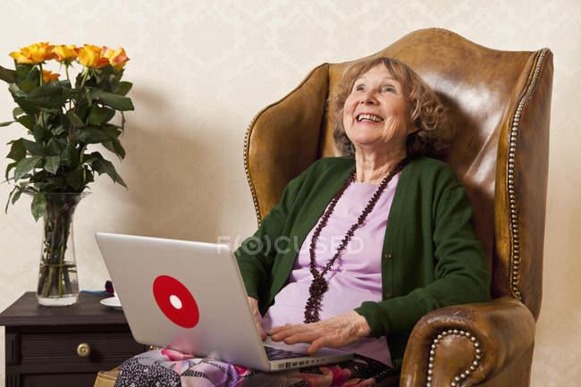 Rire femme âgée en utilisant un ordinateur portable dans un fauteuil à la maison — Photo de stock