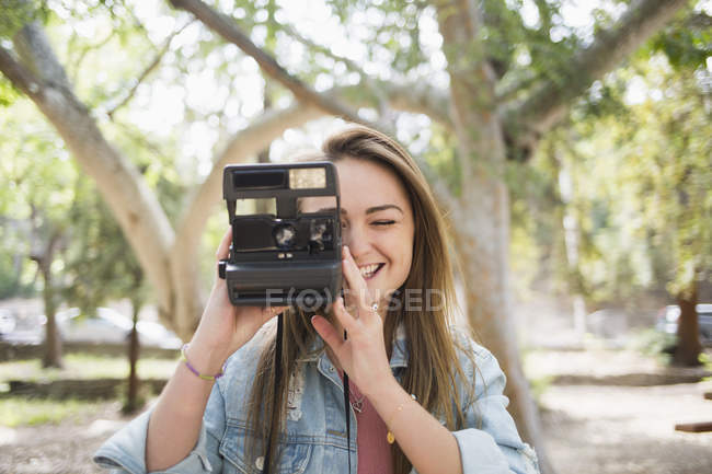 Happy young woman using instant camera in park — Stock Photo